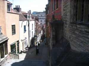 A narrow street, with steps going down a hill.