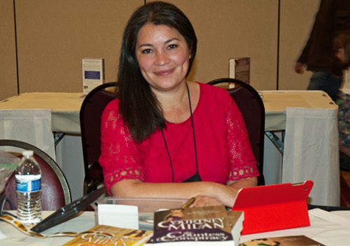 Courtney wearing a fuchsia dress sitting at a table with a book in front of her, ready for signing