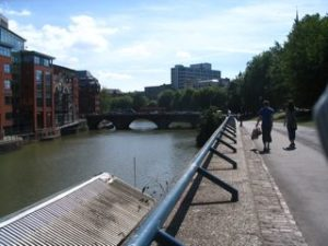 Bristol's floating harbor: a wide canal, with modern buildings on one side and a stone walking path on the other.