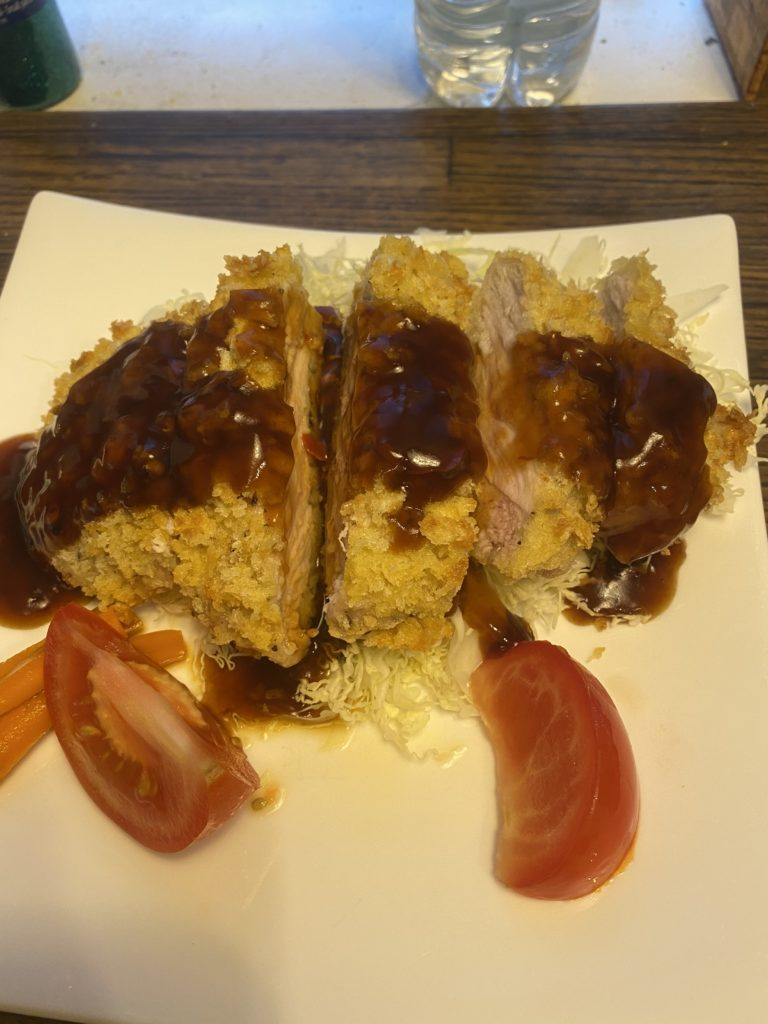 A cutlet of pork drizzled with Wedgeford Brown, over shredded cabbage, with tomato wedges