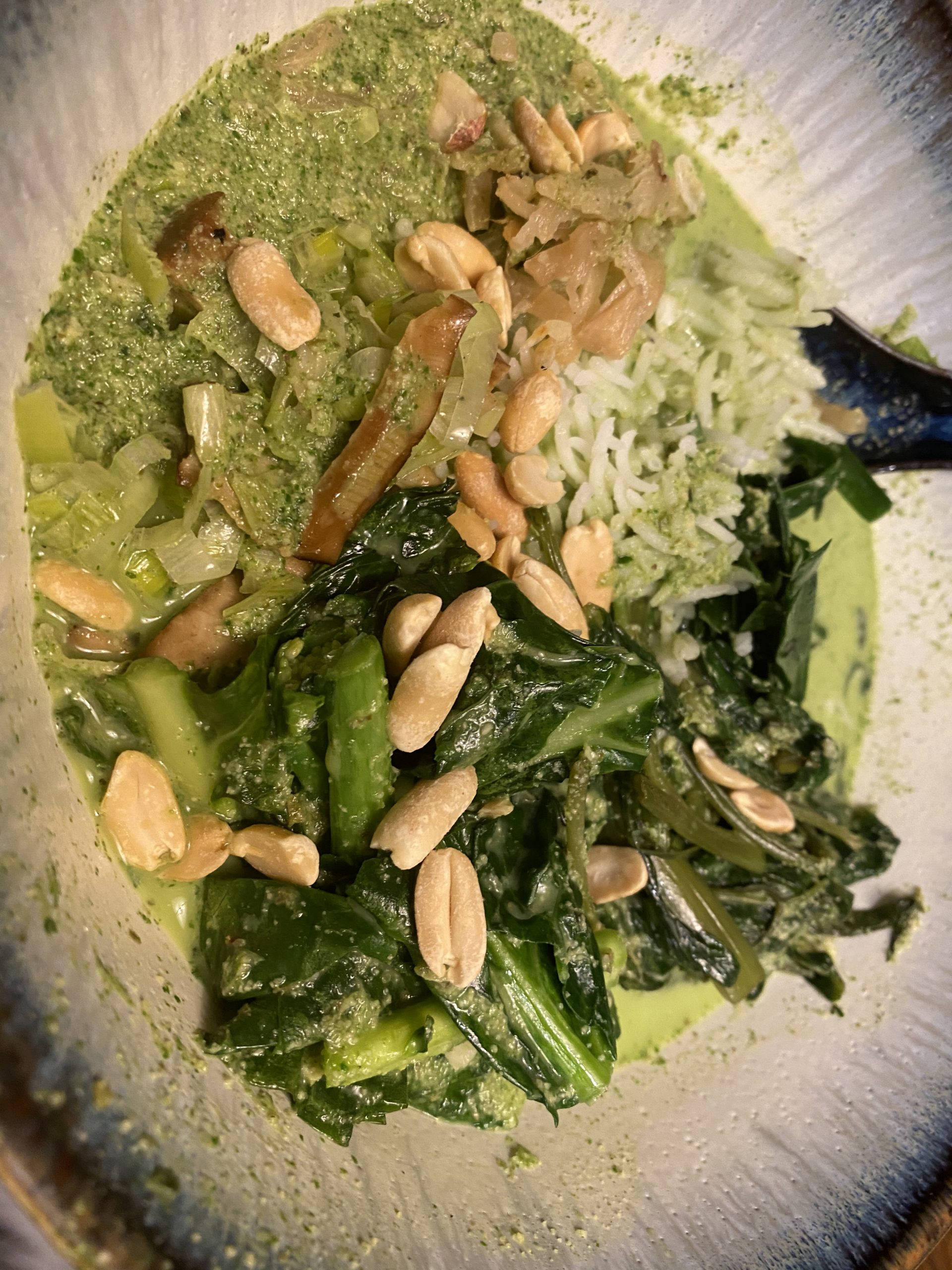 A bowl of liu cha fan: rice, vegetables, a green tea soup, and peanuts on the top